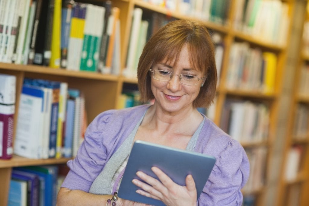 Female librarian in library reading book