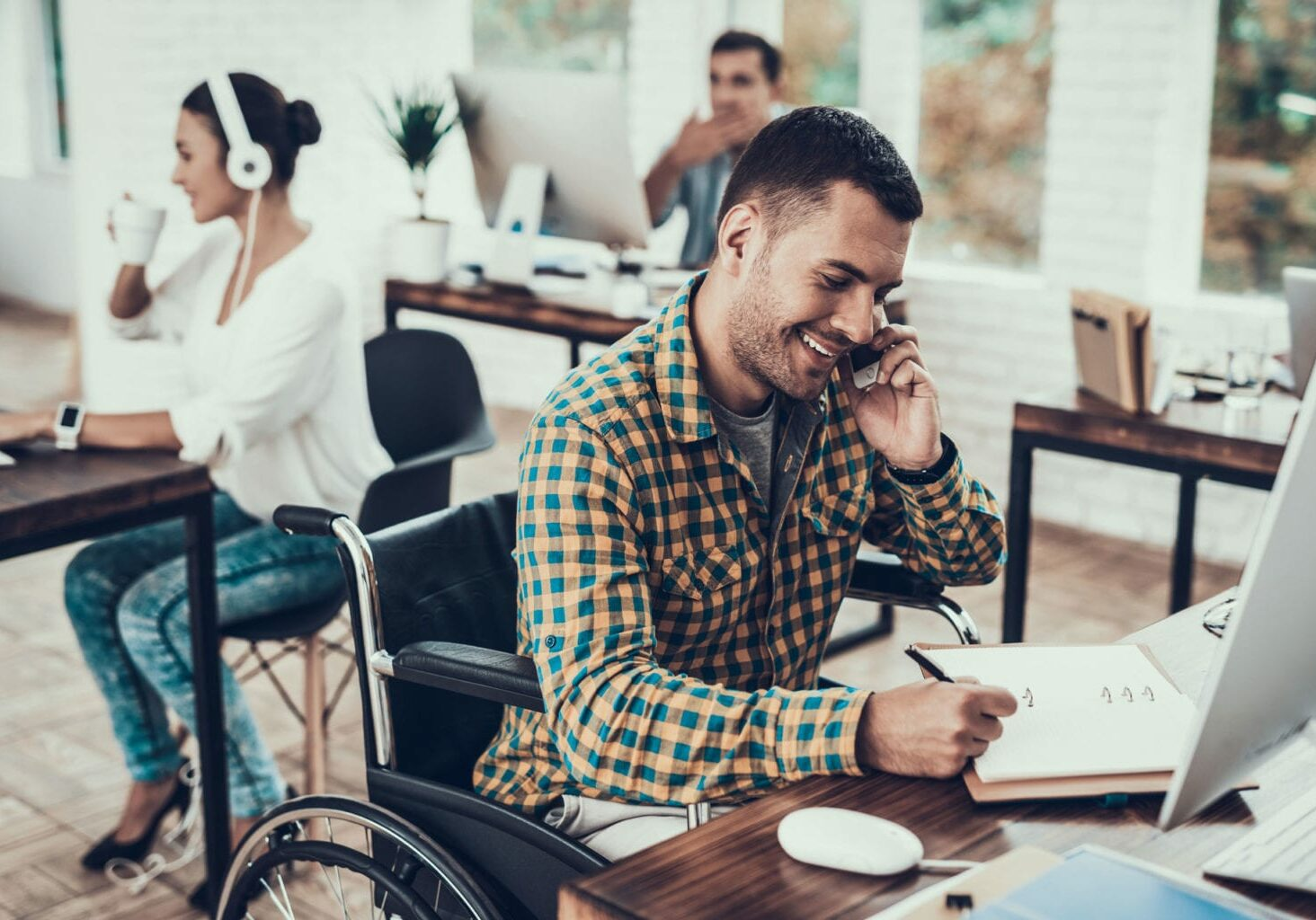 man at desk with wheelchair
