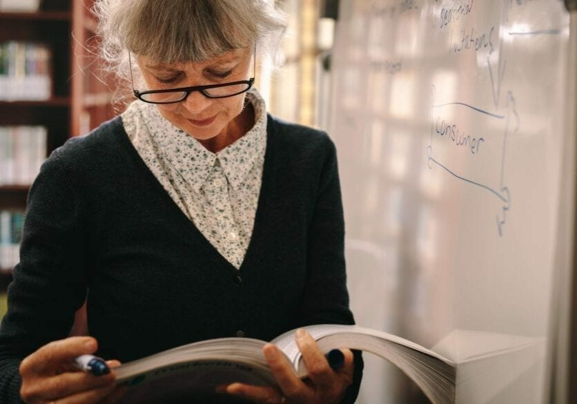 Older lady looking at textbook standing by whiteboard
