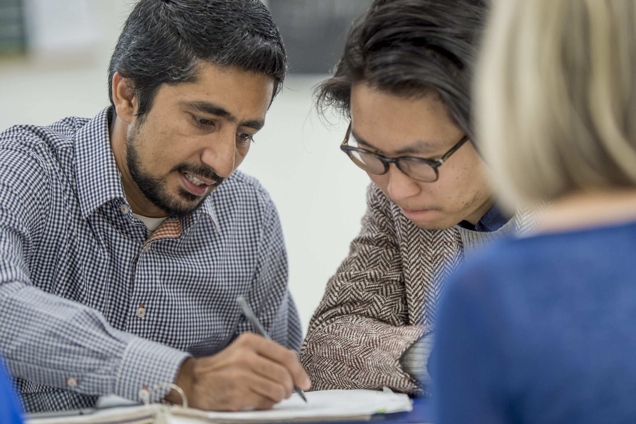 A multi-ethnic group of adults are studying together after class. They are in a university classroom taking continuing adult education classes.