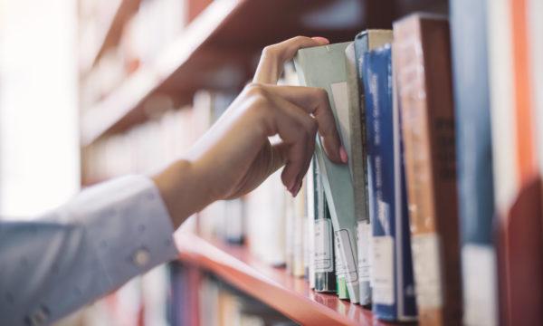 Hand picking a book off a bookshelf
