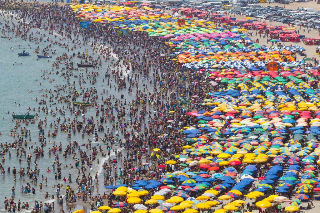crowded beach with umbrellas